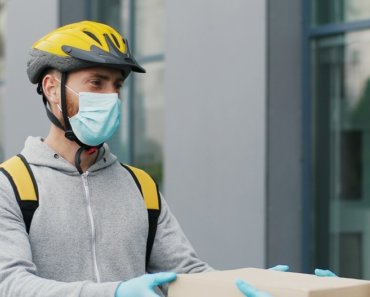 Young male courier in medical mask bringing carton boxes to woman on street and tapping on phone to check parcel. Food delivery service concept
