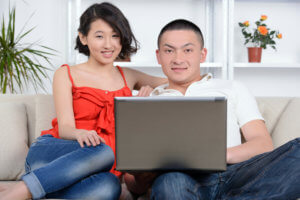 Portrait of young Asian couple sitting on sofa at home, using laptop computer, smiling and learning how to budget for a month