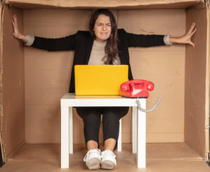 beautiful businesswoman sits in a tight paper office, needs more space, pushes the walls - Upgrade Your Home-Based Business Space