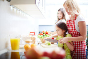 Portrait of happy mother and two daughters cooking in the kitchen - why it's important Finding Energy-Efficient Appliances