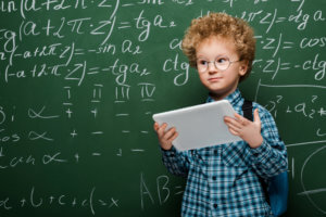 Smart child holding a computer tablet in front of a chalkboard with complex mathematical on a chalkboard - Canadian value investing is shifting to the Robo Advisor
