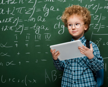Smart child holding smartphone with blank screen and touching g