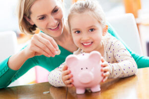 image of mother and daughter with a piggy bank saving money - How to Save for your Next Vacation without Compromising your Quality of Life.