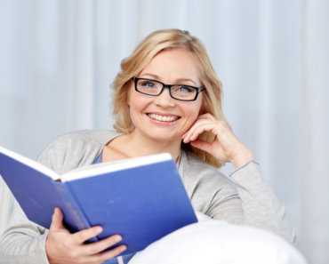 smiling middle aged woman reading book and sitting on couch at home learning How to Take Your Career to the Next Level