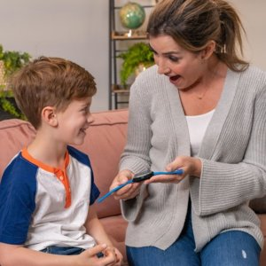 A young mother giving her son a smartwatch - Understanding Real From Fake in Kids Smartwatches